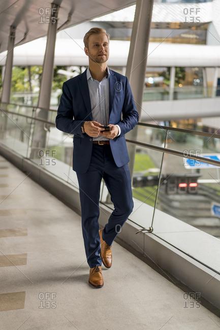 Young businessman on pedestrian bridge