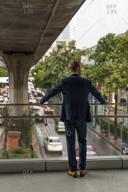 Rear view of young businessman on pedestrian bridge