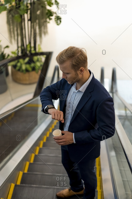 Young businessman with a coffee to go checking the time on escalator