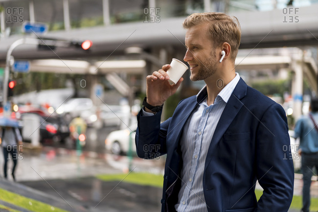Young businessman with coffee to go in Bangkok during a rainy day