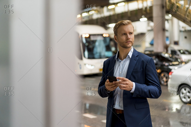 Young businessman in the Bangkok during a rainy day
