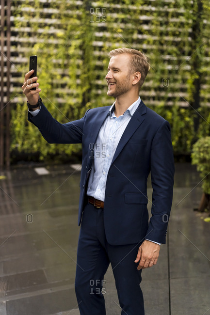 Young businessman taking a selfie with smartphone during a rainy day in Bangkok