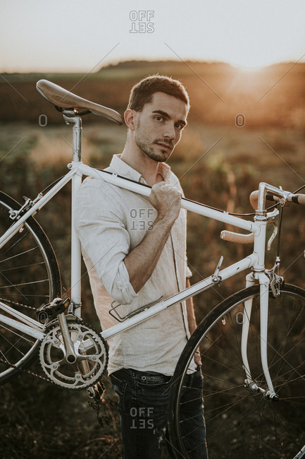 Pensive young man carrying a racing cycle in the sunshine
