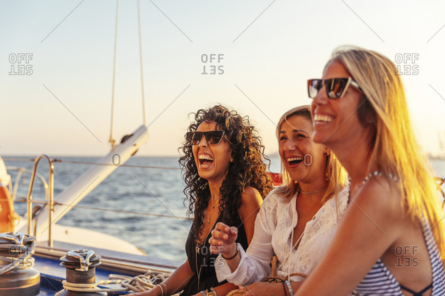 Friends laughing during boat trip in the evening light