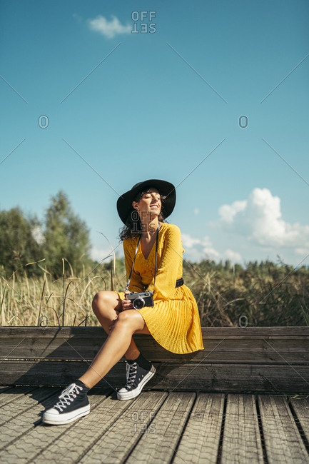 Young woman wearing a black hat and yellow dress with an analog camera sitting on wooden boardwalk
