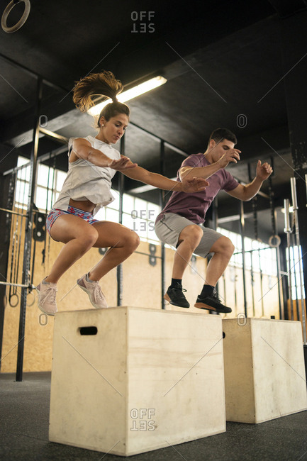 Young couple doing box jump exercise during cross training