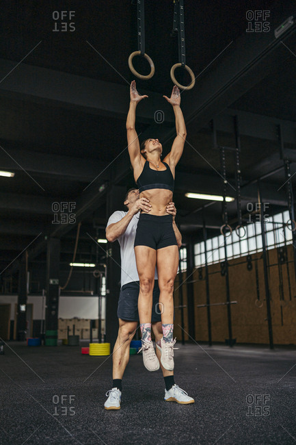 Young woman jumping to gymnastic rings- man helping her