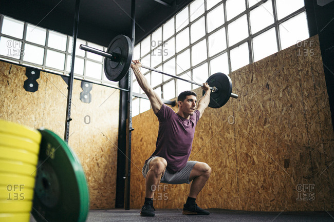 Young man doing overhead squat exercise at gym