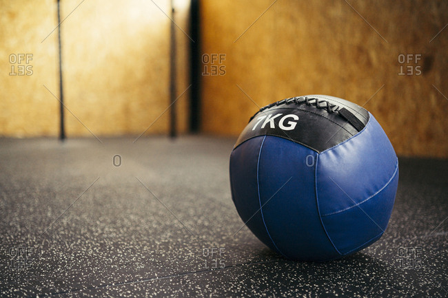 Blue medicine ball in a corner of a gym