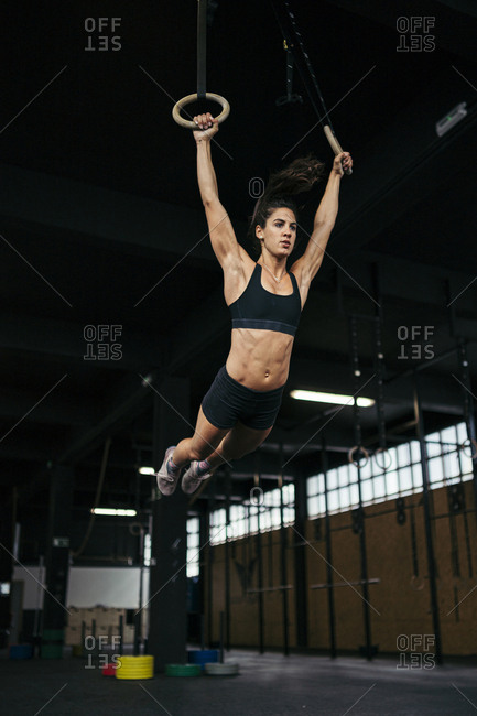 Young woman wearing black sportswear doing ring muscle up workout with gymnastic rings