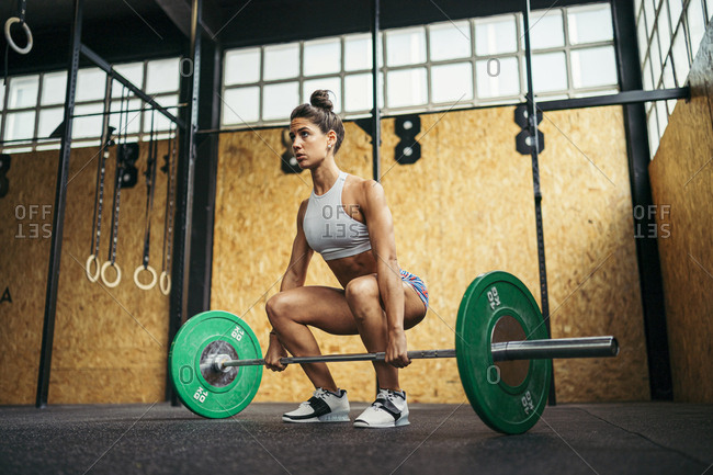 Young woman doing overhead squat exercise at gym