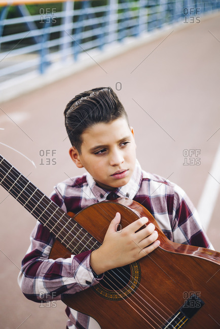 Gypsy boy with guitar on a bridge