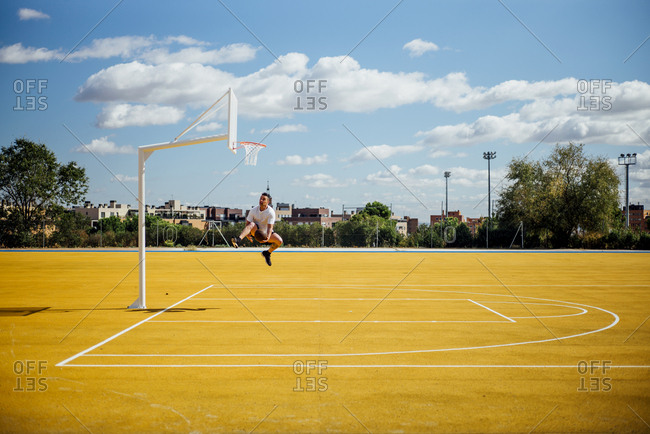 Man playing basketball on yellow court- dunking