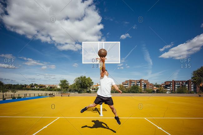 Man playing basketball on yellow court- dunking