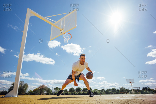 Man playing basketball on yellow court- dribbling