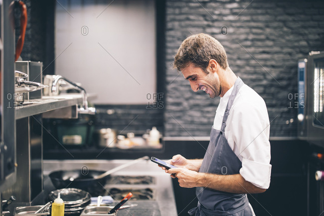 Smiling cook using smartphone in the kitchen of a restaurant
