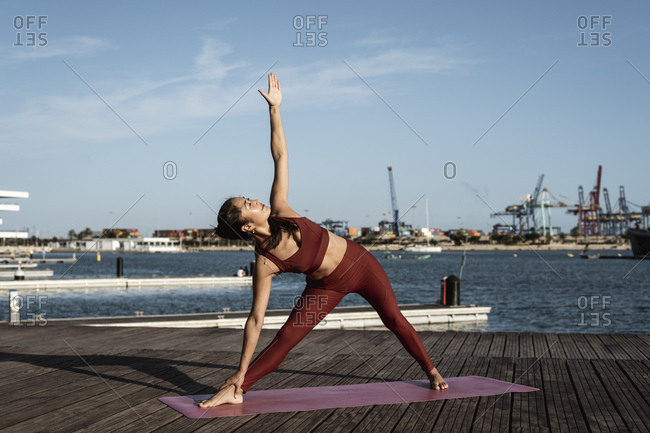 Asian woman practicing yoga at harbor- triangle pose