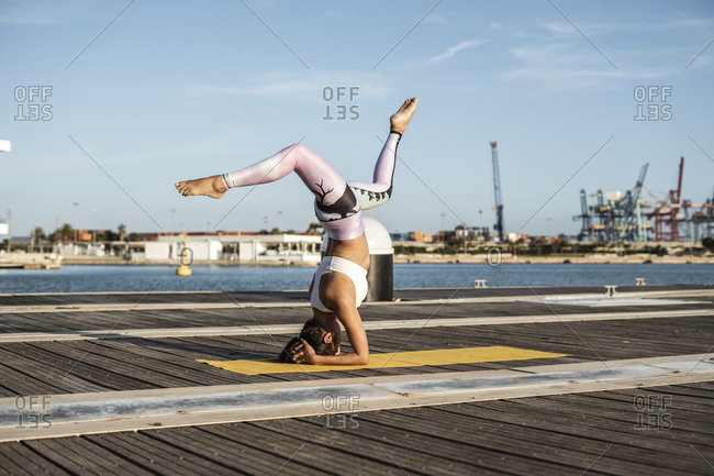 Asian woman practicing yoga on a pier at harbor- headstand with split