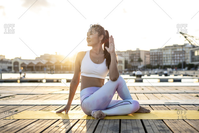 Asian woman practicing yoga on a pier at harbor- half-spinal twist at sunset