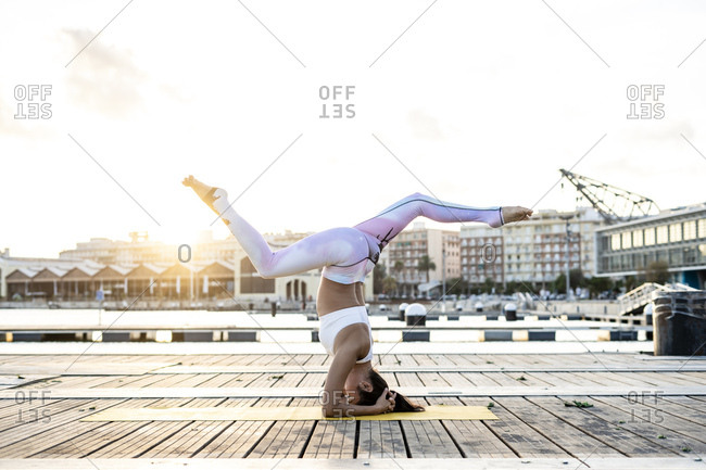 Asian woman practicing yoga on a pier at harbor at sunset- headstand with split