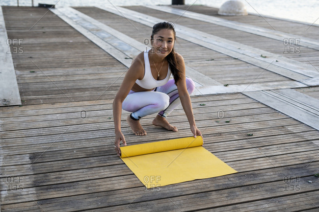 Asian woman practicing yoga on a pier at harbor- rolling out her yellow yoga mat