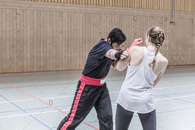 Female boxer sparring with coach in sports hall
