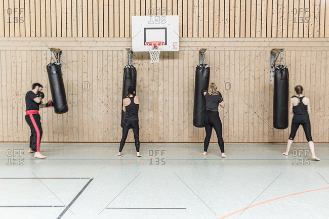 Coach and female boxers practicing at punchbags in sports hall
