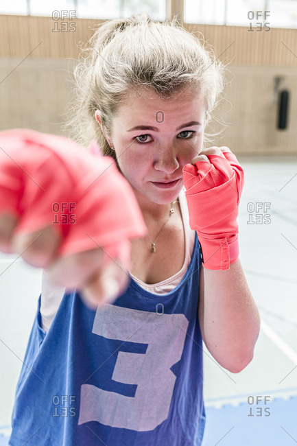 Portrait of confident female boxer in sports hall