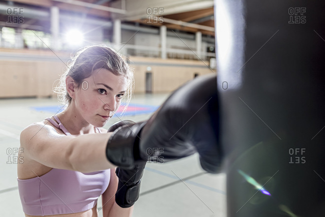 Female boxer practicing at punchbag in sports hall