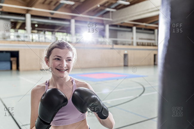 Smiling female boxer practicing at punchbag in sports hall