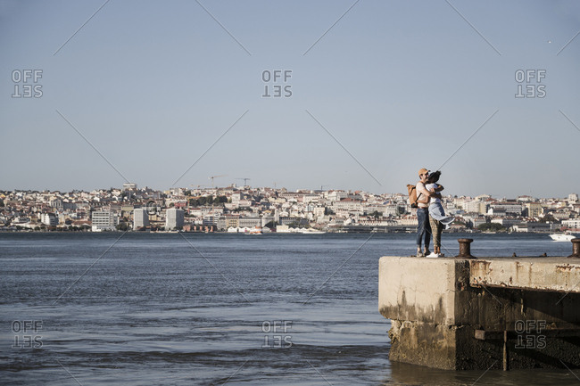 Young couple hugging on pier at the waterfront- Lisbon- Portugal