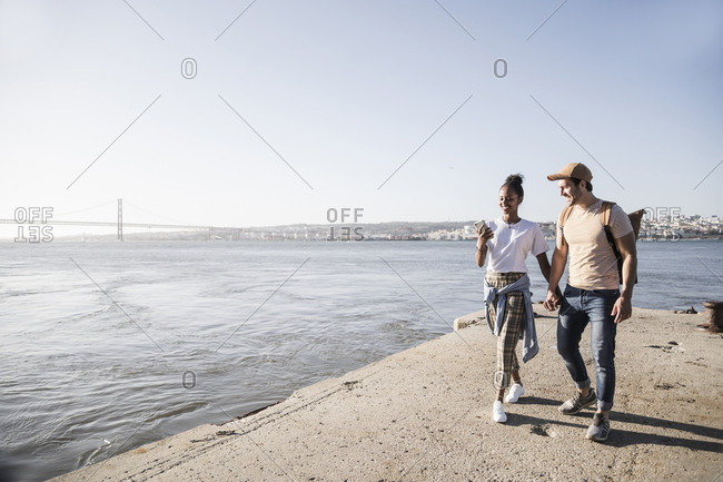 Young couple with cell phone on pier at the waterfront- Lisbon- Portugal