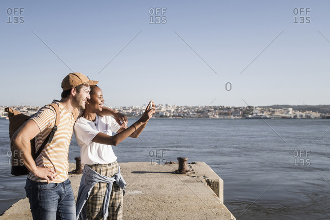 Happy young couple taking a selfie on pier at the waterfront- Lisbon- Portugal