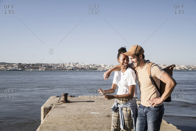 Happy young couple using cell phone on pier at the waterfront- Lisbon- Portugal