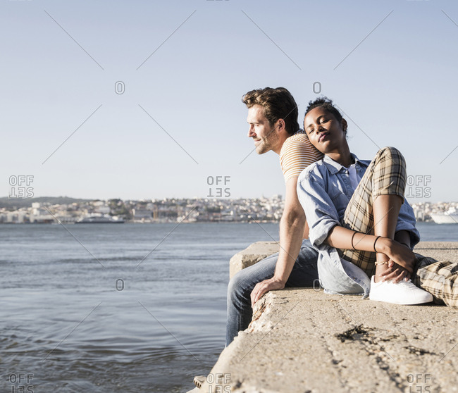Young couple sitting on pier at the waterfront- Lisbon- Portugal