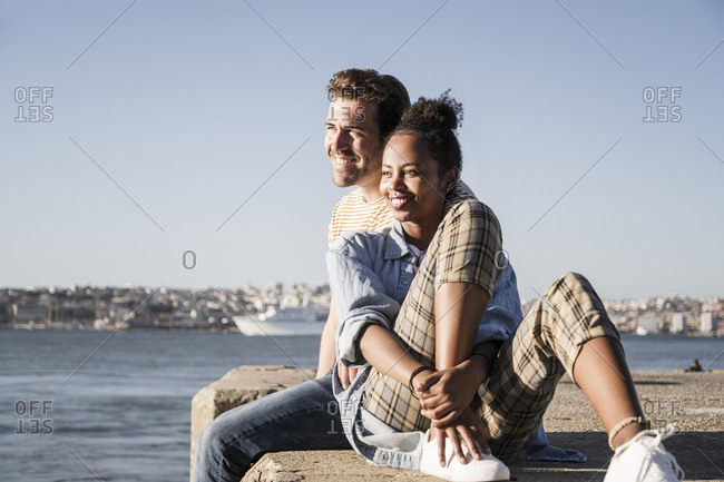 Happy young couple sitting on pier at the waterfront- Lisbon- Portugal