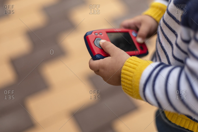 Hands of little boy holding toy mobile phone- close-up