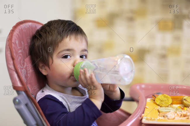 Portrait of little boy sitting on high chair drinking water from flask