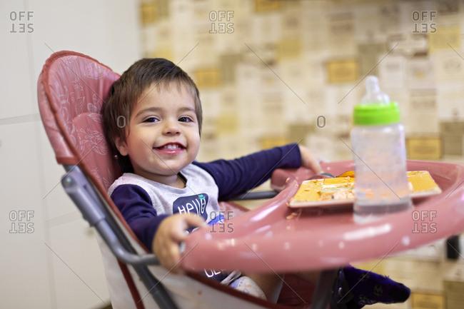 Portrait of happy little boy sitting on high chair