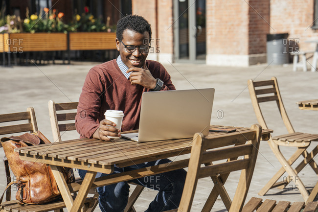 Young man using laptop in a coffee shop- drinking coffee