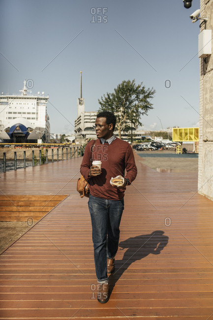 Young man with coffee cup and hamburger walking at the harbor