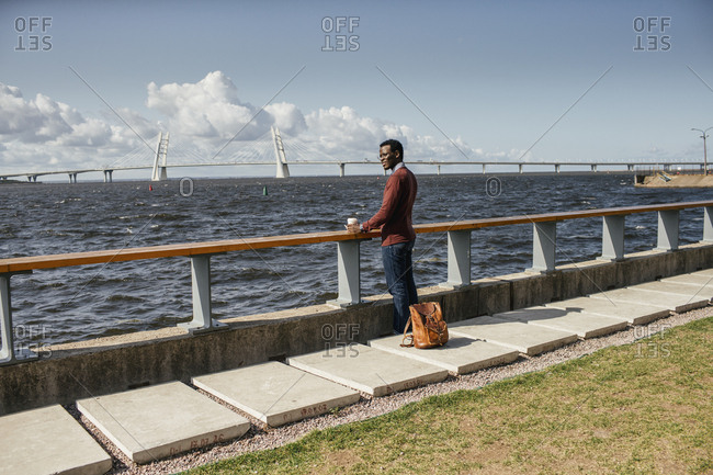 Young man sitting on railing at the sea- eating hamburger- drinking coffee