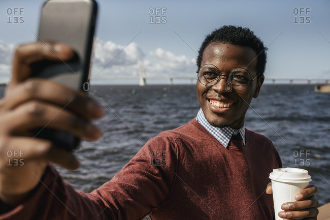 Young man taking smartphone selfie at the sea- holding take out coffee
