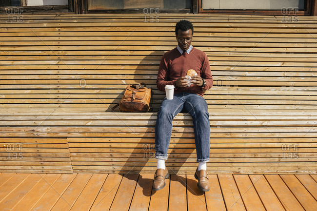 Young man sitting on wooden bench- eating hamburger- drinking coffee