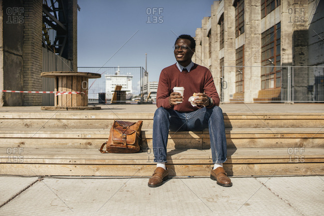Young man sitting on stairs in the city- eating hamburger- drinking coffee