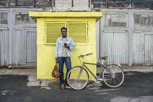 Young man with smartphone- waiting in front of yellow junction box