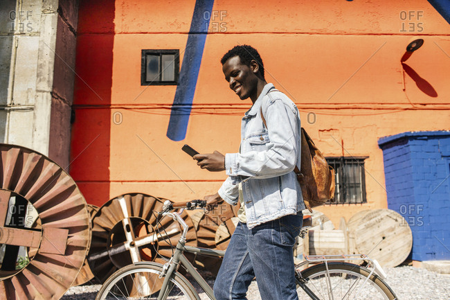 Relaxed young man commuting in the city with hos bicycle- using smartphone