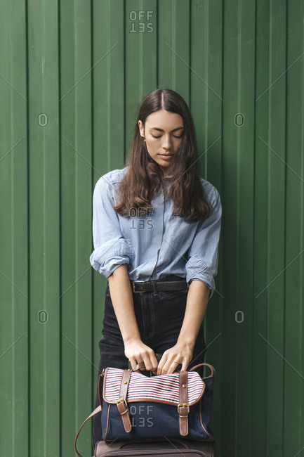 Young traveler leaning on green wall at station
