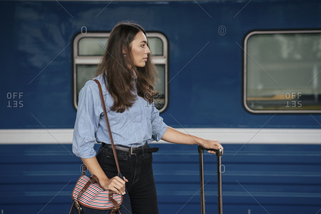 Young female traveler waiting on train station- looking sideways