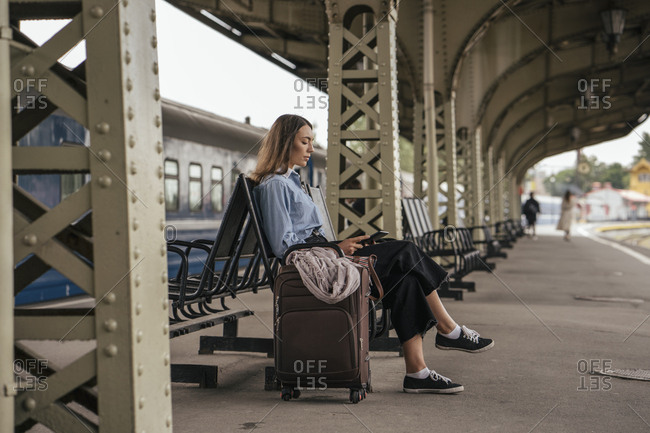 Young female traveler waiting on train station- using e-book